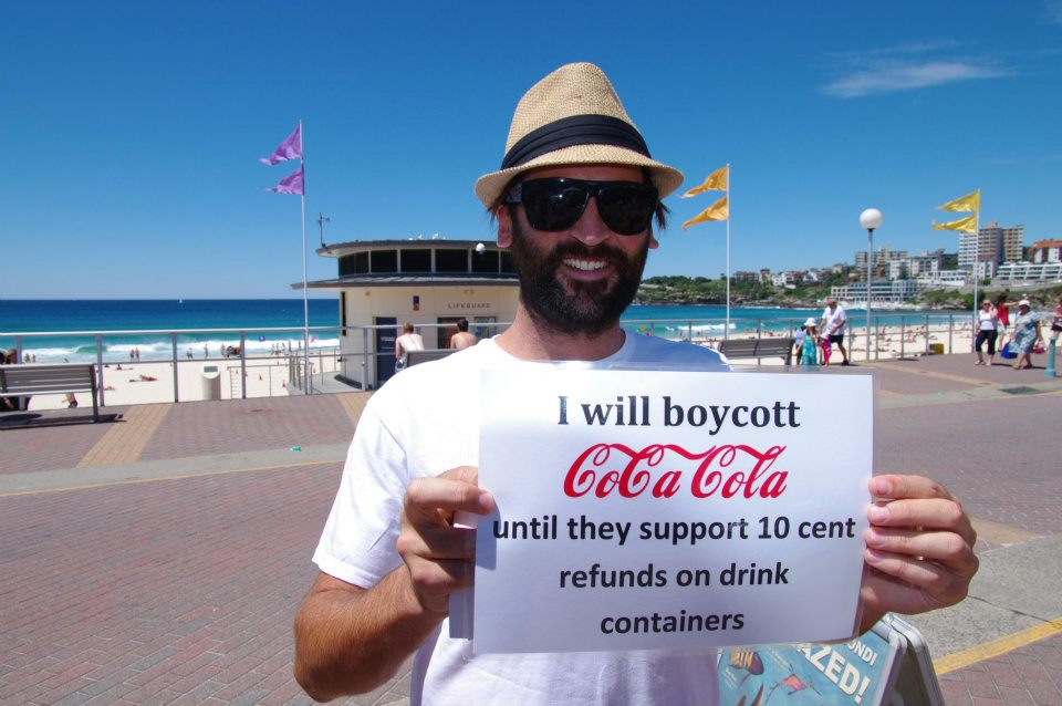 CDS campaigner Tim Silverwood holds a sign reading 'I will boycott Coca Cola until they support 10 cent refunds on drink containers'.